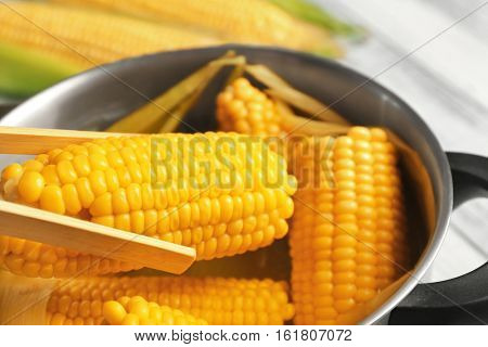 Wooden tongs taking tasty boiled corncob from saucepan, close up