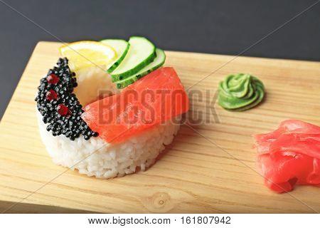 Sushi doughnut on wooden cutting board closeup