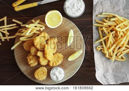 Tasty chicken nuggets with fries, lemon and sauce on cutting board