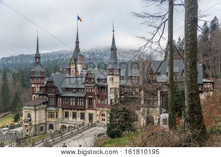 Neo-Renaissance Pelesh castle (Sinaia Romania) against frosted forest background.