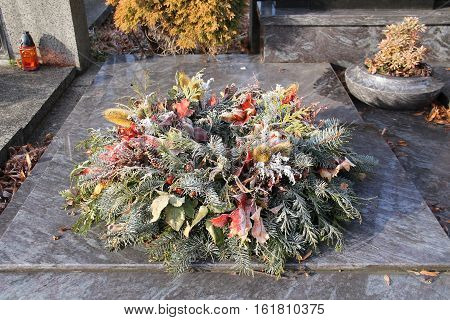 funeral wreath decorated with coniferous twigs and sear plants and leaves on the cemetery covered with hoarfrost
