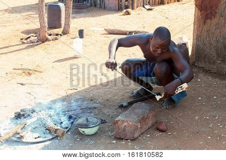 Himba Man Adjusts Wooden Souvenirs