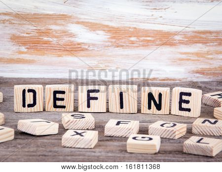 Define from wooden letters on wooden background.
