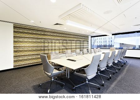 Conference room with chairs and large office window under flashing light