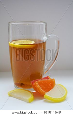 glass of tea with lemon and colored pieces of marmalade