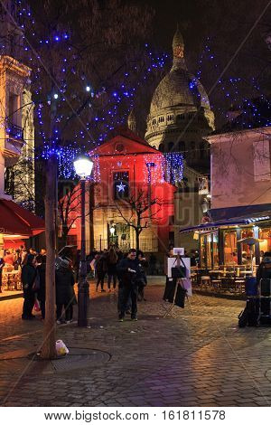 Paris, France, January 12, 2014. Christmas lights in Montmartre, Paris, Place du Tertre with the Sacre Coeur in the background.