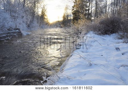 Little stream in the light of the midwinter sun just over horizon in the middle of the day in the North of Sweden.
