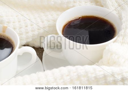 Cup With Hot Coffee Wrapped In A White Woolen Scarf