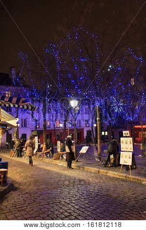 PARIS FRANCE - January 12, 2014. Place du Tertre in Montmartre at night with street artists ready to paint tourists.