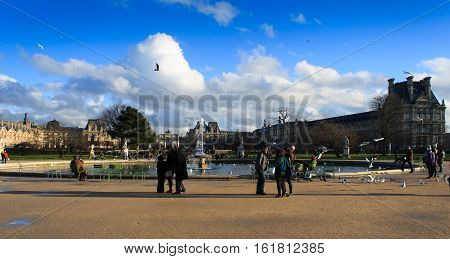 Paris, France, January 13, 2014. People sitting and walking at the fountain close to Arc de Triomphe du Carrousel and Louvre.