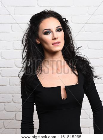 pretty cute sexy girl or beautiful young woman with fashion makeup on serious face and curly long brunette hair in black dress with deep neckline on white brick wall background