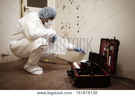 Police technician at work on evidences of blood stains