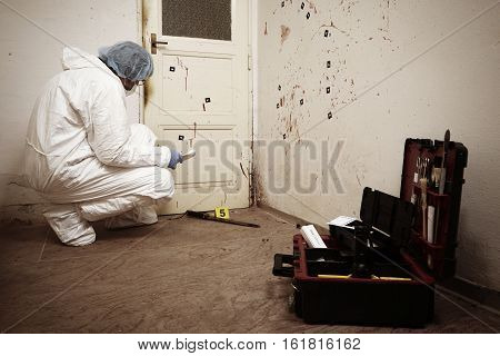 Criminologist collecting evidences of blood stains on location
