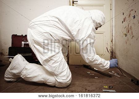 Criminologist technician collecting evidences of blood stains on floor