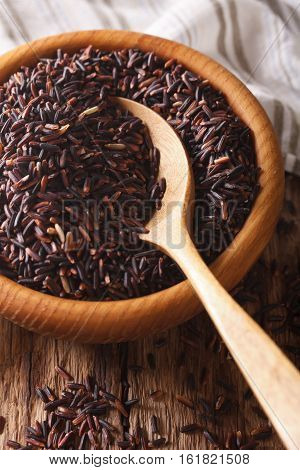 Unpolished Wild Long Black Rice Close Up In A Wooden Bowl. Vertical