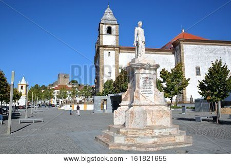 CASTELO DE VIDE, PORTUGAL - OCTOBER 14, 2016: Statue of  Dom Pedro V with the church of Santa Maria da Devesa and the castle in the background