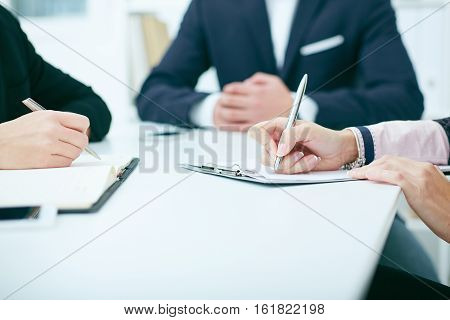 Close-up of hands of business meeting. Female hands holding a silver pen closeup. Buiness woman making notes at office workplace.