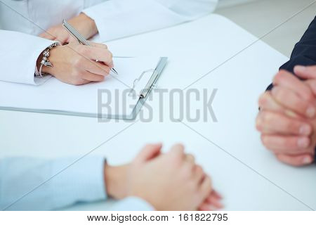 Close up of patients hands and doctor taking notes. Ward round patient visit check medical calculation and statistics concept. Physician ready to examine patient
