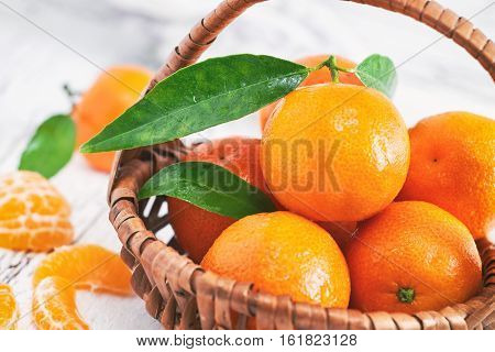 Fresh clementines with leaves in woven basket on white rustic wooden background
