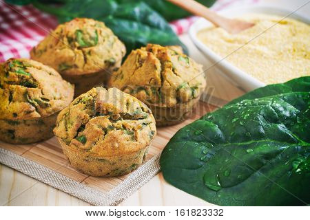Vegan muffins with spinach and corn flour on wooden background
