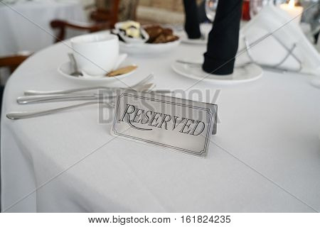Reserved label on the decorated table with tableware. Selective focus. Copy space.