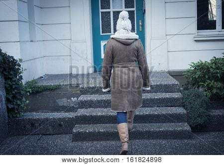 A young woman is ascending - go up on the steps. A young woman is willing to go home. On the front door outside a house
