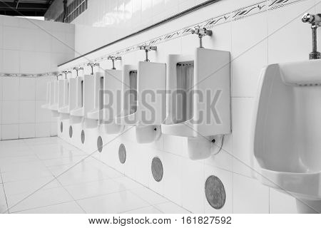 New row of outdoor urinals men public toilet