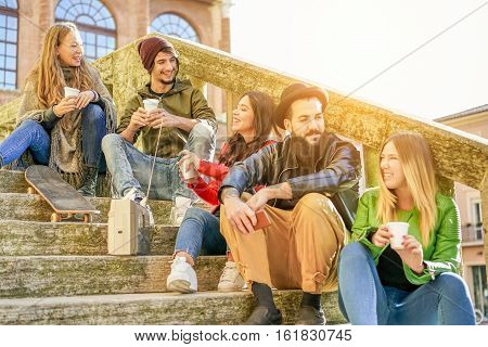 Happy friends toasting coffee take away and listening music from vintage stereo - Young people having fun in city university center - Study and friendship concept - Warm filter - Focus on left guys