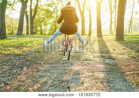 Happy woman riding vintage red italian style bicycle with her legs in the air - Girl having fun in park outdoor with back sun light - Freedom concept - Warm filter with focus on bike wheel