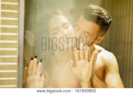 Young couple having romantic tender moments in hotel shower - Reflection view of young people kissing and showing love - Sexual and romance concept - Focus on girl nose mouth - Warm filter