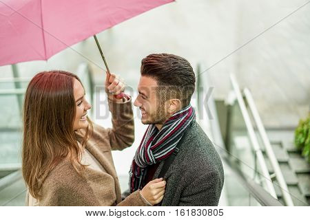 Happy couple having tender moments under a umbrella in rainy day outdoor - Young people smiling going outside of mall shopping center - Love and relationship concept - Focus on woman eye - Warm filter