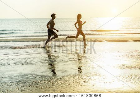 Silhouette of young happy couple running on seashore splashing water with back sun light - Two cheerful lovers having fun on the beach - Love and vacation concept - Focus on him - Warm filter