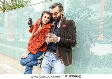 Hipster happy couple surfing in social network web sites - Fashion people looking for the last trends online - Love for clothes and accessories concept - Focus on woman - Warm vivid filter