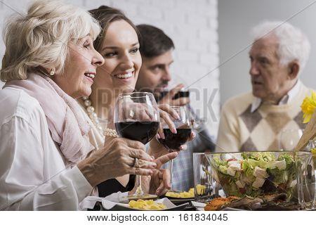 Women Drinking Wine During Family Dinner