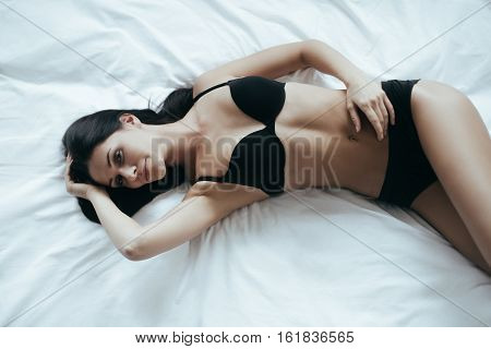 Something crazy on her mind. Top view of irresistible young woman in black lingerie posing seductively and looking at camera while lying on the bed at home