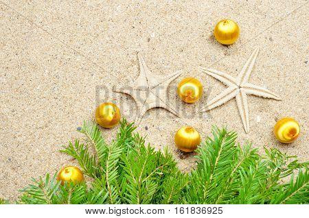 Christmas decorations starfish with Christmas balls on the sand