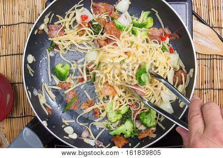 Chef stir fried Spaghetti with tongs / cooking spicy spaghetti concept
