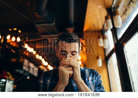 Young Man Is Sitting In The Restaurant And Tasting A Warm Drink.