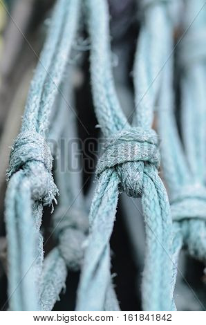 Fraying knots on old fishing boat net