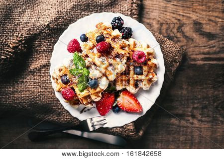 Belgian waffles with strawberries blueberries and syrup on wooden table