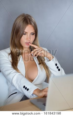 Sexy business woman or secretary with notebook computer pc wearing white suit with decollete big breast sitting on chair against copy space gray wall background web camera chating surfing internet looking in monitor.