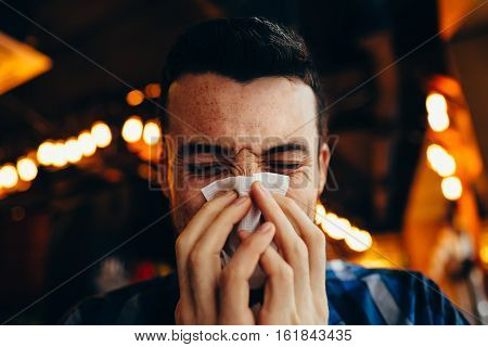 Attractive Young Man Blowing His Nose