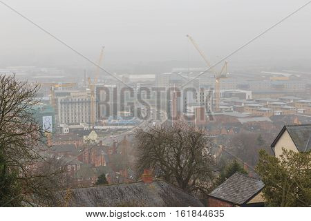LINCOLN ENGLAND - DECEMBER 15: Construction cranes in the fog on large commercial development projects. In Lincoln England. On 15th December 2016.