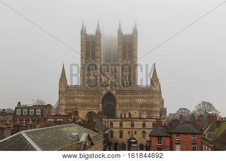 LINCOLN ENGLAND - DECEMBER 15: West face of Lincoln Cathedral on a foggy day. In Lincoln England. On 15th December 2016.