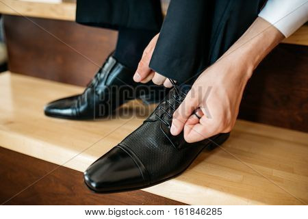 Man ties the laces on his polished shoes. Business formal dress style. Official event, perhaps a wedding. Cropped image