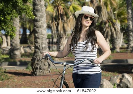 Young beautiful woman in sunglasses and hat with bike having good time in Lanzarote, Spain.