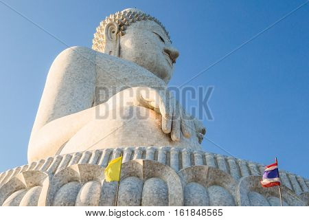 Perspective view from below of the popular Big Buddha on Nakkerd hills of Ao Chalong in Phuket, Thailand in a sunny day. Symbol of peace and spirituality.