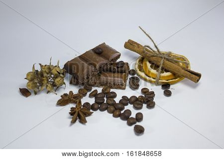 composition of chocolate, coffee, cinnamon and dried orange on a white background