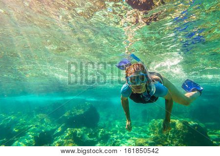 Close up of female apnea swims in tropical turquoise sea of Racha Noi, Phuket in Thailand.
