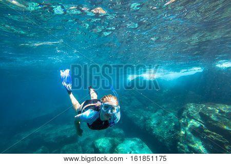 Female apnea swims in deep waters of the popular Similan Islands in Thailand, Andaman Sea.